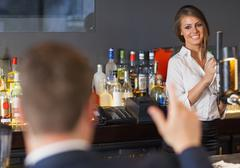 Handsome man ordering a drink from gorgeous waitress Stock Photos