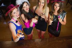 Happy gorgeous women holding flutes of champagne having hen party Stock Photos