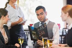 Handsome businessman ordering dinner from waitress Stock Photos