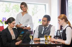 Three business people ordering dinner from waitress Stock Photos