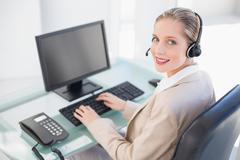 Stock Photo of Smiling blonde call centre agent typing