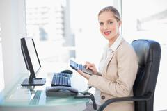 Side view of smiling blonde businesswoman using calculator Stock Photos