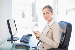 Content blonde businesswoman text messaging Stock Photos