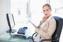Stock Photo of Thoughtful blonde businesswoman using tablet