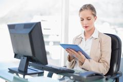 Concentrated blonde businesswoman using tablet - stock photo