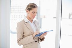 Stock Photo of Focused blonde businesswoman using tablet pc