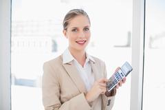 Smiling blonde businesswoman using calculator Stock Photos