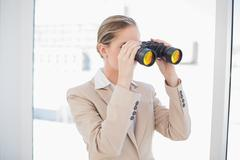 Serious blonde businesswoman looking through binoculars Stock Photos