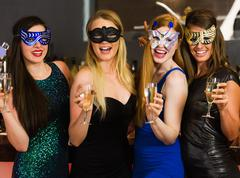 Stock Photo of Laughing friends wearing masks holding champagne glasses
