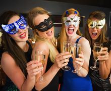 Stock Photo of Attractive friends with masks on holding champagne glasses