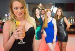 Stock Photo of Blonde attractive woman holding cocktail standing in front of her friends