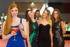 Attractive woman holding cocktail standing in front of her friends - stock photo