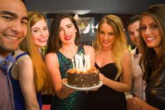 Happy friends celebrating brithday one holding birthday cake Stock Photos