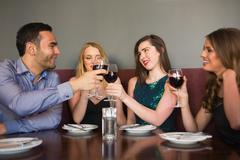 Friends clinking red wine glasses at a bar - stock photo