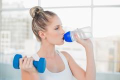 Peaceful sporty blonde drinking water while lifting dumbbell Stock Photos