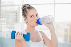 Sporty blonde drinking water while lifting dumbbell - stock photo