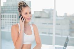 Pensive sporty blonde on the phone - stock photo