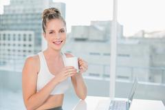 Smiling athletic blonde holding coffee Stock Photos