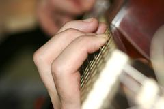 Fingers on guitar neck Stock Photos