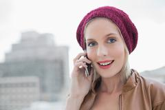 Surprised casual blonde on the phone outdoors - stock photo
