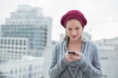Smiling pretty blonde text messaging outdoors - stock photo