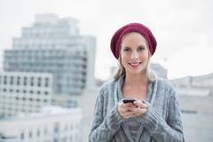 Happy pretty blonde text messaging outdoors - stock photo