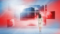 Rear view of businesswoman looking at screens showing server towers - stock illustration