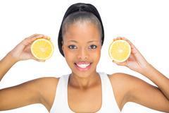 Smiling woman holding slices of orange - stock photo