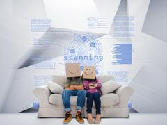 Couple with cartons on head sitting on couch under blue holographic finger print - stock photo