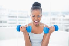 Woman working out with dumbbells - stock photo