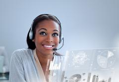 Cheerful woman with headset using futuristic interface hologram - stock photo