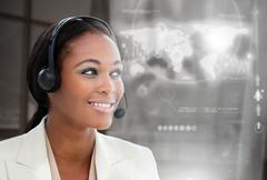 Smiling pretty businesswoman using futuristic interface hologram - stock photo