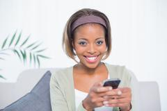 Cheerful elegant woman sitting on sofa text messaging - stock photo