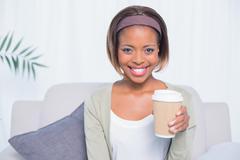 Smiling woman sitting on sofa holding coffee - stock photo
