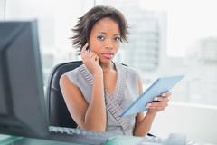 Stock Photo of Businesswoman using her digital tablet at desk