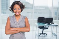 Smiling businesswoman standing in office and crossing her arms Stock Photos