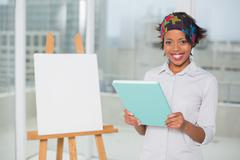 Smiling artistic woman holding sketchpad - stock photo