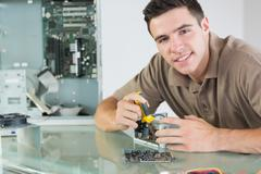 Handsome smiling computer engineer repairing hardware with pliers - stock photo