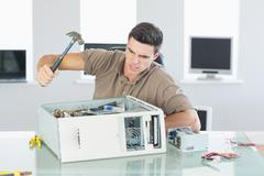Attractive angry computer engineer destroying computer with hammer - stock photo