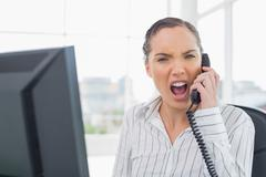 Angry businesswoman screaming on telephone while looking at camera - stock photo