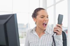 Stock Photo of Angry businesswoman screaming at phone