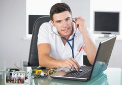 Stock Photo of Handsome smiling computer engineer examining laptop with stethoscope