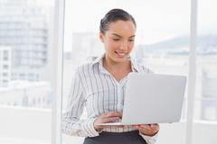 Stock Photo of Businesswoman standing and typing on a laptop