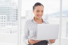 Content pretty businesswoman using laptop - stock photo