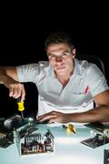 Stock Photo of Attractive computer engineer working by night with screw driver
