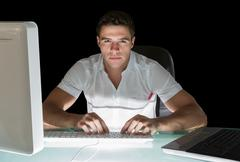 Handsome frowning computer engineer working at night - stock photo