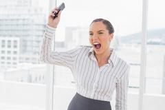 Offended businesswoman screaming and throwing her mobile phone Stock Photos