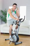 Stock Photo of Cheerful handsome man training on exercise bike phoning