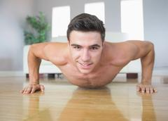 Happy handsome man doing push ups - stock photo