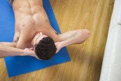 Overhead view of attractive man doing sit ups Stock Photos